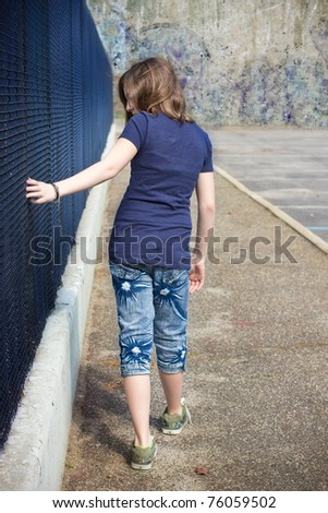 Urban scene of a teenage girl running her hand along a fence with a grunge wall in the distance