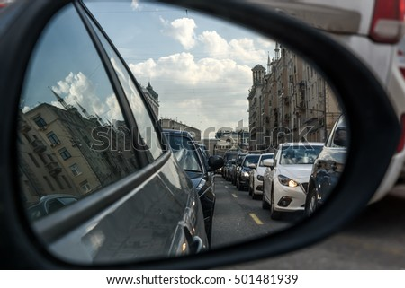 Urban scene with traffic jam on a road in the city at rush hour in a car mirror