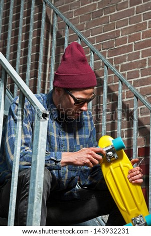 Urban skateboarder with woolen hat and sunglasses holding his board sitting on iron stairs. - stock photo