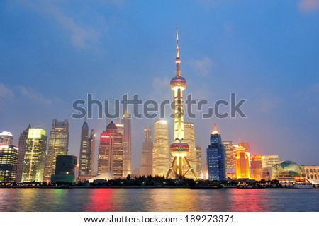 Urban skyscrapers in Shanghai at night over river - stock photo