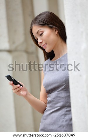 Urban smart casual businesswoman using app on smartphone. Young Asian Caucasian adult woman touching smart phone using 3g 4g app to read online or sms texting. - stock photo