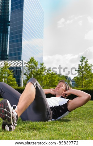 Urban sports - young man is doing warming up and sit-ups before running in the city on a beautiful summer day
