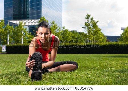 Urban sports - young woman is doing warming up before running in the city on a beautiful summer day - stock photo