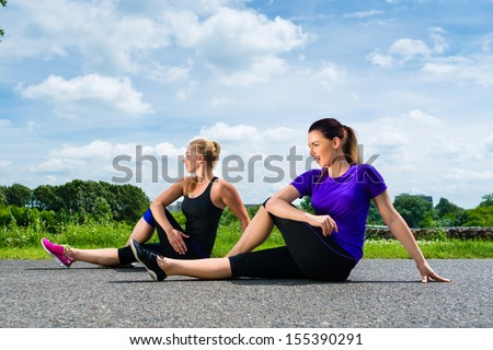 Urban sports - young women doing warming up together before running in the greenfield on a summer day - stock photo