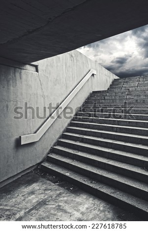 Urban staircase in underground passage with exit to dark stormy sky. - stock photo