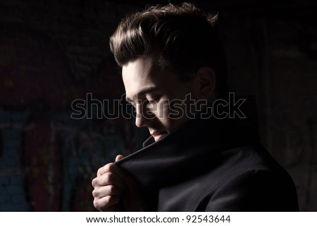 Urban style handsome young man with fifties hairstyle dressed in black - stock photo