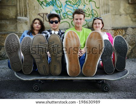 Urban stylish trendy young teenage people with legs on skate - stock photo