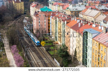 Urban train going along bright colored vintage residential buildings in Vysehrad district in Prague, Czech republic - urban background - stock photo