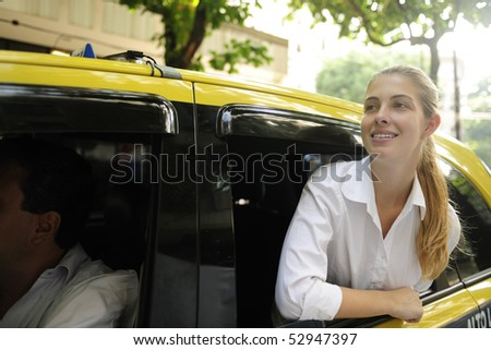 urban transport: happy female passenger inside of a taxi - stock photo