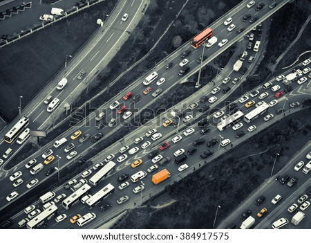 Urban transportation - rush hour traffic on a city roads. Modern metropolis with intersection of the traffic trails on a highway. Traffic jams of roadside, transportation motion in a big city.
