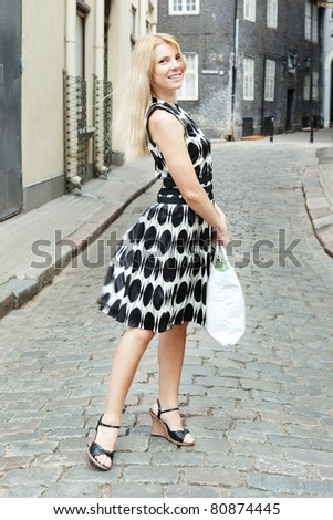 Urban view of attractive young girl with big bag - stock photo