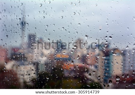 Urban view of rain drops falls on a window during a stormy day overlooking Auckland CBD New Zealand skyline in the background. - stock photo