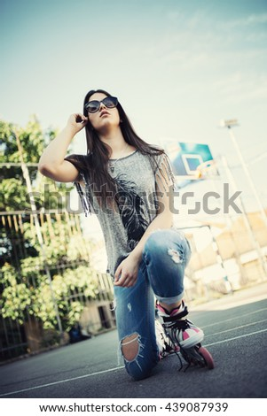 Urban vintage portrait of beautiful and attractive girl with sunglasses and roller skates. Warm summer colors and haze. Strong backlight.