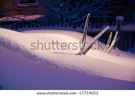 Urban wintry night scene, cars on parking lot screen-wipers sticking out of snow - stock photo
