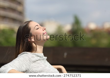 Urban woman sitting on a bench of a park and breathing deep fresh air - stock photo