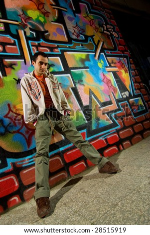 Urban young man and graffiti background - stock photo