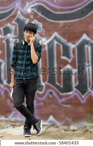 Urban youth talking on mobile phone in front of wall with graffiti - stock photo