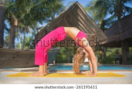 urdhva dhanurasana.photo of the girl doing yoga by the pool in a - stock photo