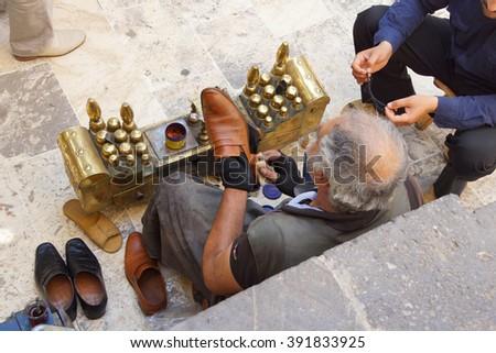 URFA, TURKEY - JUN 8, 2014 - Shoe shine man works  in Urfa bazaar,  Turkey - stock photo