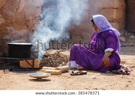 Urfa, Turkey - September 20, 2009:Unidentified woman cooks in the courtyard of her house while her children working on the field as agricultural workers.Most of the time she also works in the fields - stock photo