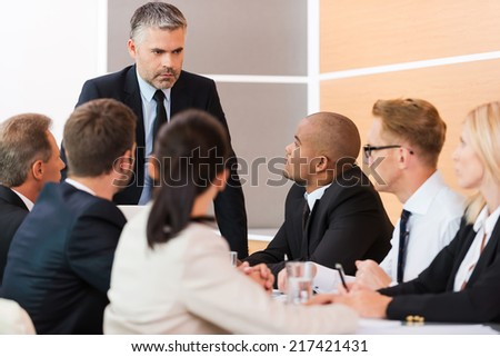 Urgent business meeting. Business people in formalwear sitting at the table together while their boss standing and looking at them  - stock photo