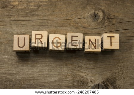 urgent text on a wooden background - stock photo