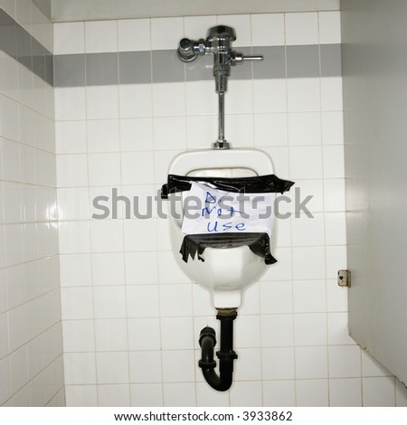 Urinal in men's bathroom with an out of order sign taped on it. - stock photo
