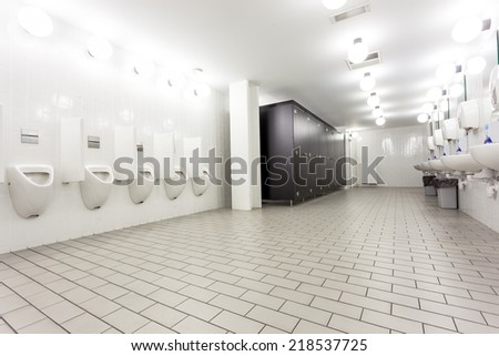 urinals and toilets in an old building for men only - stock photo