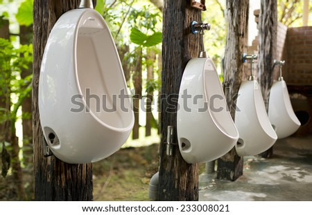Urinals hanging on tree high and low near forest - stock photo