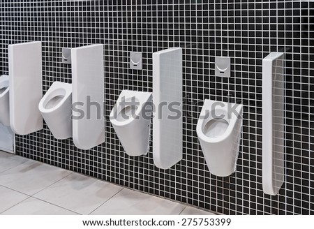 urinals in a public toilet. Focus on the central Urinals - stock photo