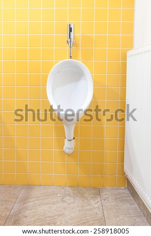 urinals in an old building for men only - stock photo