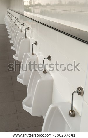 Urinals in the men's bathroom with white ceramic urinals design of white men in the toilet. Oblique/Canted angle shot. - stock photo