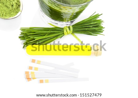Urine sample in test tube, pH litmus paper test strip, ground wheatgrass powder and fresh barley grass isolated on white background. Natural herbal medicine, healthy living. - stock photo