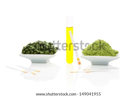 Urine sample in test tube, pH test strips, green pills and green ground powder isolated on white background.  - stock photo