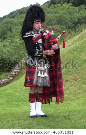 URQUHART CASTLE, SCOTLAND, UK - CIRCA AUGUST 2015: Scottish bagpiper dressed in traditional red and black tartan dress