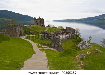 Urquhart Castle surrounded by the famous Loch Ness - stock photo