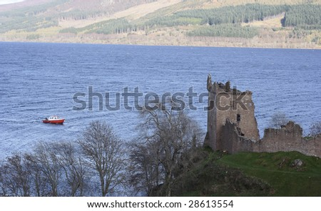 Urquhart Castle with a boat approaching on Loch Ness - stock photo