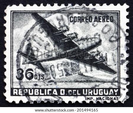 URUGUAY - CIRCA 1958: a stamp printed in the Uruguay shows Four-Motored Plane, circa 1958 - stock photo