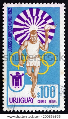 URUGUAY - CIRCA 1972: a stamp printed in the Uruguay shows Torchbearer, 20th Summer Olympic Games, Munich 72, circa 1972 - stock photo