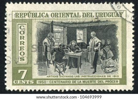 URUGUAY - CIRCA 1952: stamp printed by Uruguay, shows Artigas Dictating Instructions, circa 1952 - stock photo