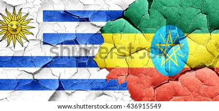 Uruguay flag with Ethiopia flag on a grunge cracked wall - stock photo