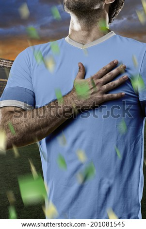 Uruguayan soccer player, listening to the national anthem with his hand on his chest. On a stadium. - stock photo