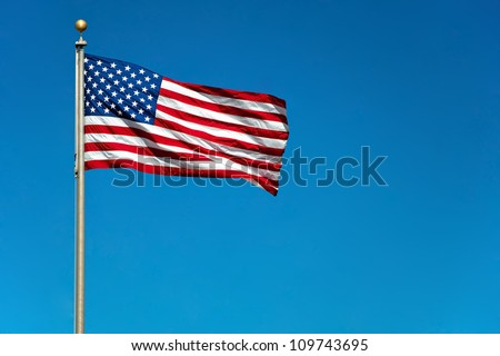 US American flag waving in the wind with beautiful blue sky in background - stock photo
