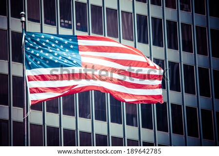 US american symbol flag over blue modern city buildings  - stock photo