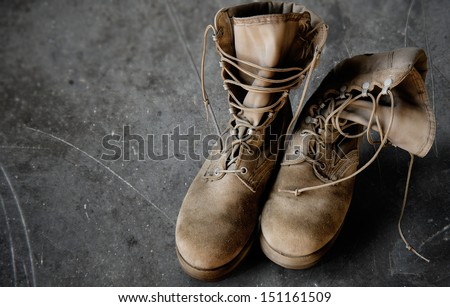 US Army boots on the scratched gray floor (Memorial day, Veteran's day, 4th of july, Independence day) - stock photo