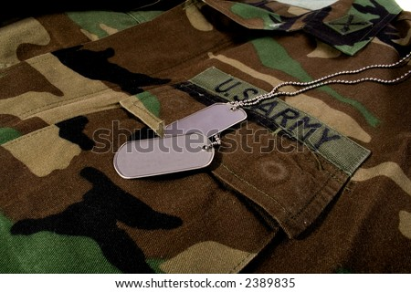 US Army camouflage with blank dog tags, and artillery officer collar insignia - stock photo
