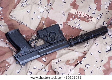us army special operation handgun with silencer on camouflage background - stock photo