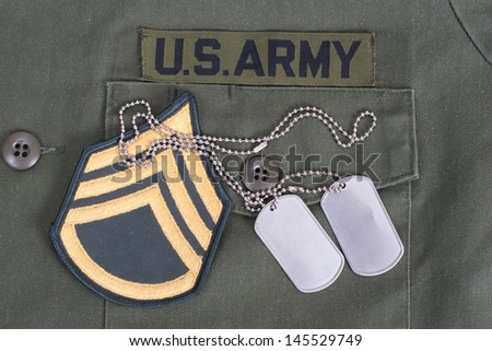 us army uniform with blank dog tags and sergeant rank patch - stock photo