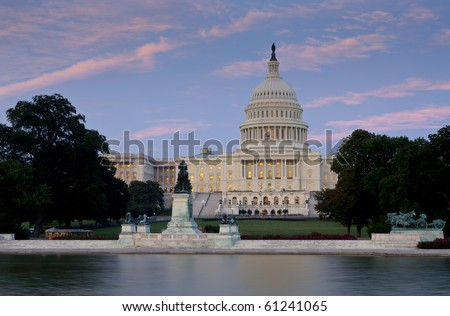 US Capitol at dusk from across reflecting pool. Focus on capitol dome and building.