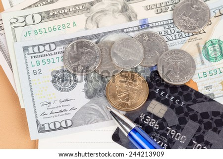 US coins and banknotes with credit card and pen - stock photo
